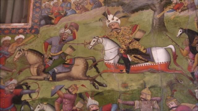vídeos de stock, filmes e b-roll de cu zi mural representing battle at chehel sotoun pavilion, isfahan, iran - montar um animal