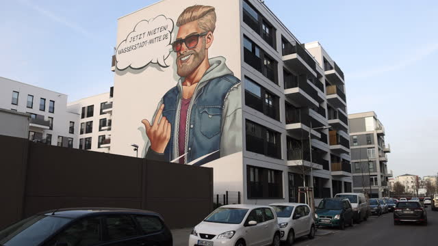"""mural showing a young man with a beard and sunglasses with the headline """"now rent"""" at the facade of a relatively new luxury apartment building in the... - hipster person stock videos & royalty-free footage"""