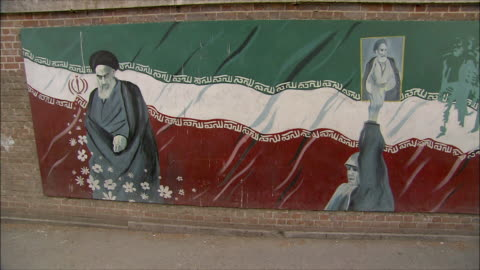 vidéos et rushes de ms pan mural with ayatollah khomeini and iranian flag on wall in front of united states embassy, tehran, iran - mur d'enceinte