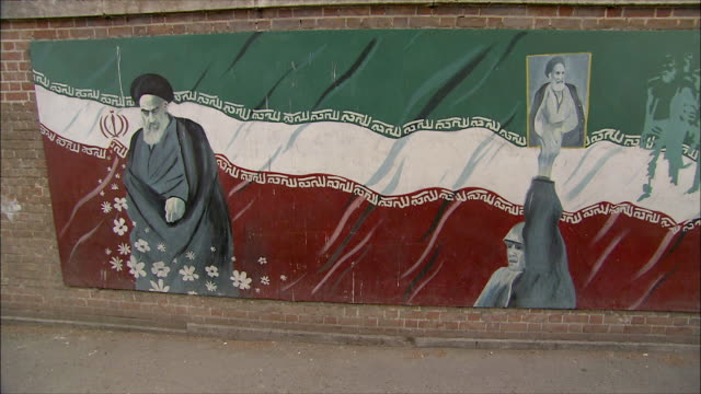 ms pan mural with ayatollah khomeini and iranian flag on wall in front of united states embassy, tehran, iran - vox populi stock videos & royalty-free footage