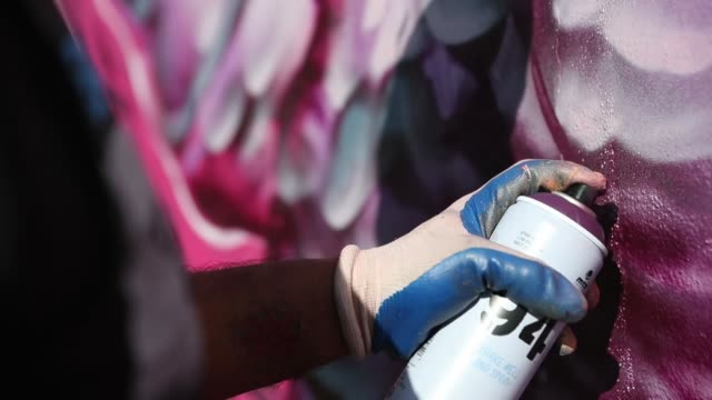 muralist caesar perez uses spray paint to create his art on the side of a building as the wynwood neighborhood prepares for the annual art basel art... - spray painting stock videos & royalty-free footage