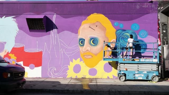 muralist cloe hakakian spray paints her art on the side of a building as the wynwood neighborhood prepares for the annual art basel art fair on... - joe 03 stock videos & royalty-free footage