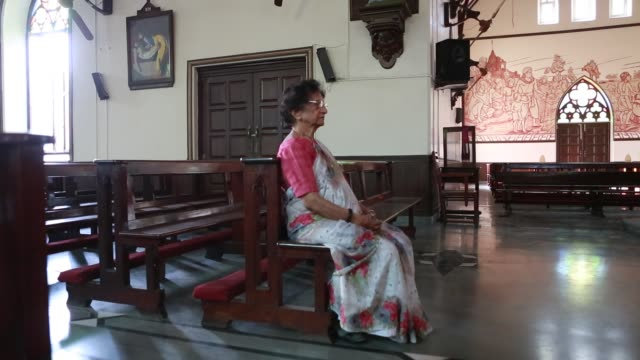 Murals of Angelo da Fonseca in St Xavier's Church in Pune India at the walls of the church His wife Ivy Muriel is sitting in a pew in front of the...