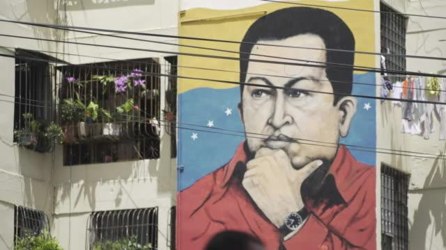 murals of late venezuelan president hugo chavez and current president nicolas maduro in caracas - ウゴ・チャベス点の映像素材/bロール