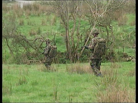 murder trial; lib northern ireland: south armagh: army lynx helicopter over tilt down as lands in field seq army soldiers along thru fields and one... - county armagh stock videos & royalty-free footage
