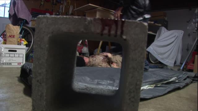 vídeos y material grabado en eventos de stock de a murderer rolls a victim onto a tarpaulin. - matar