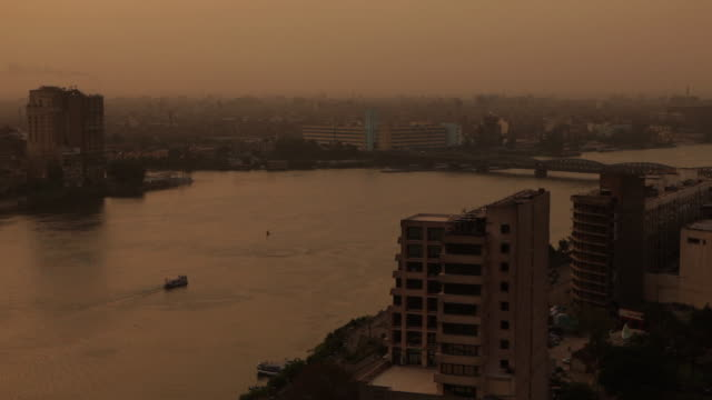 vídeos de stock, filmes e b-roll de ms murky sunset shot of nile with boat and city / cairo, egypt - áfrica do norte