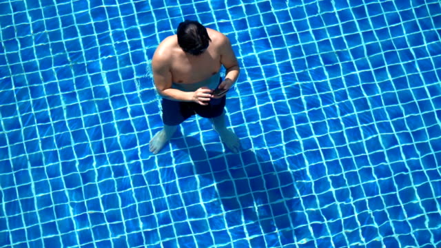 slo mo - muscle man using phone in swimming pool - e mail stock videos & royalty-free footage