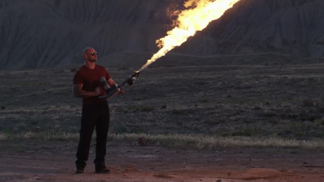 a muscled man shoots a flamethrower - tall person stock videos and b-roll footage