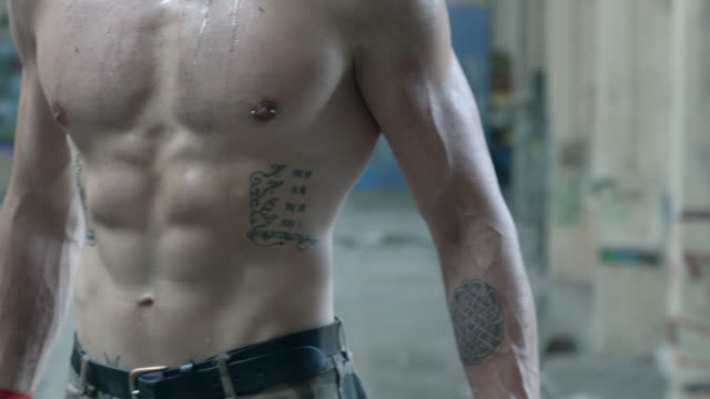 Muscles on a shirtless personal trainer man after a workout inside an abandoned building. - Slow Motion