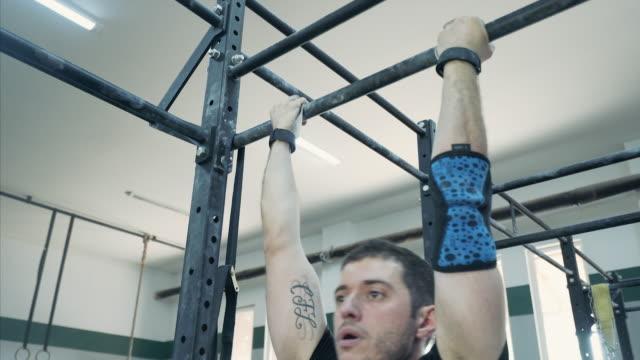musculair und zuversichtlich mann tut pullups in der turnhalle. - menschliche gliedmaßen stock-videos und b-roll-filmmaterial