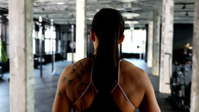 muskulöse sportler mit langhantel im fitness-studio trainieren - pferdeschwanz stock-videos und b-roll-filmmaterial