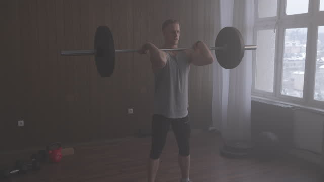 muscular athlete holding a barbell on his shoulders, doing front squats - squatting position stock videos & royalty-free footage