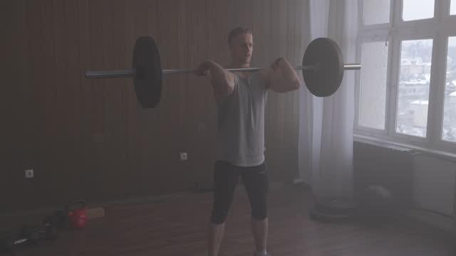 vídeos y material grabado en eventos de stock de atleta musculoso sosteniendo una barra en sus hombros, haciendo sentadillas delanteras - vista de frente
