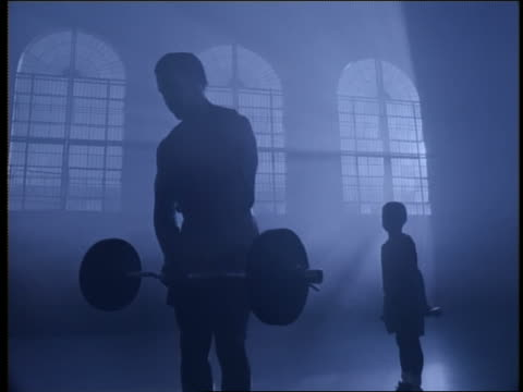 blue muscular black man lifting barbell as small boy in background lifts dumbbells in gym - body building stock videos & royalty-free footage