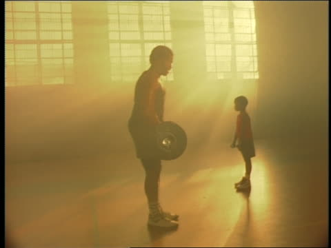 yellow silhouette muscular black man lifting barbell as small boy in background lifts dumbbells in gym - copying stock videos & royalty-free footage