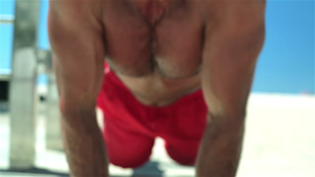Muscular Brazilian man does push-ups staring into camera on Copacabana Beach