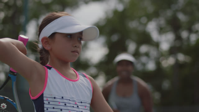 muscular female coach rates accuracy of girl tennis player during lesson - endurance stock videos & royalty-free footage