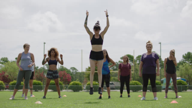 muscular female fitness trainer demonstrates a burpee to a group of athletic women during an exercise class - bodyweight training stock videos & royalty-free footage