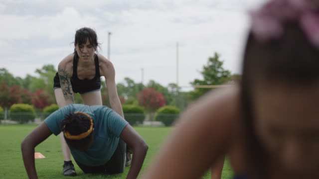 muscular female fitness trainer helps a woman with her push-up form during an exercise class on an american football field - bodyweight training stock videos & royalty-free footage