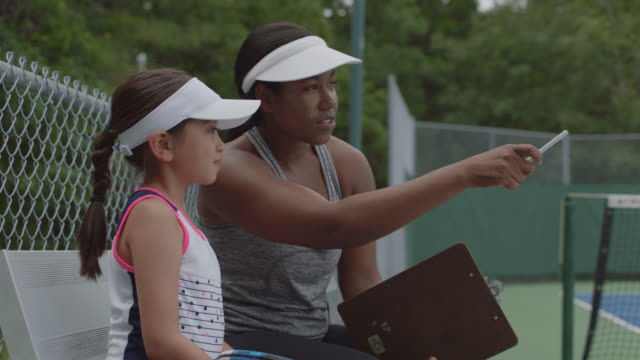 slow mo. cu. muscular female tennis coach gives a girl player tips during a practice break - manager stock videos & royalty-free footage