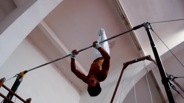 muscular gymnast performing routine on horizontal bar - horizontal bar stock videos and b-roll footage
