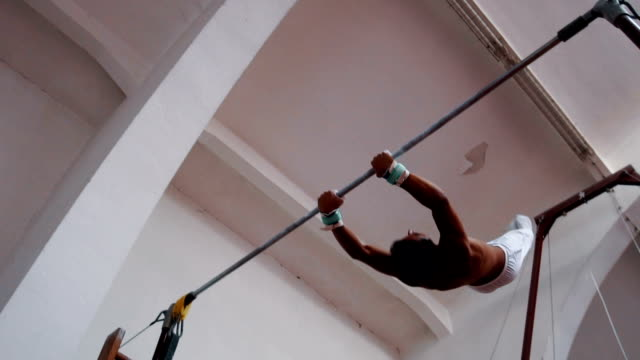muscular gymnast spining on horizontal bar - horizontal bar stock videos & royalty-free footage