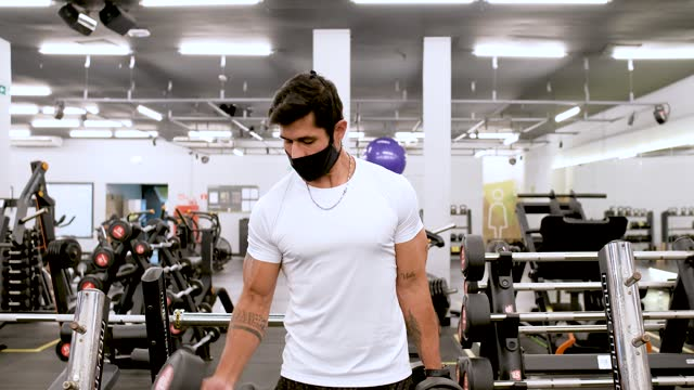 muscular latin man using dumbbell in gym with protective mask - bridle stock videos & royalty-free footage