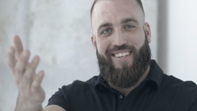 muscular male with beard smiling into camera and using welcoming hand gestures - one mature man only stock videos & royalty-free footage
