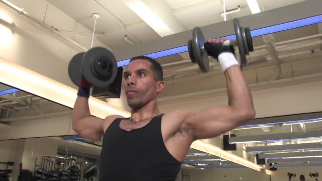 vídeos de stock e filmes b-roll de muscular homem dando haltere retroprojector prensas - one mid adult man only