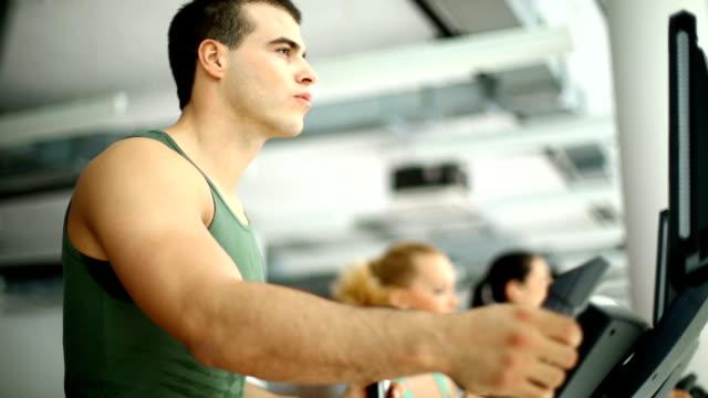 Muscular man exercising on a treadmill.