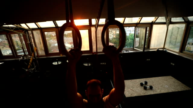muscular man exercising on gymnastic rings - gymnastic rings stock videos & royalty-free footage