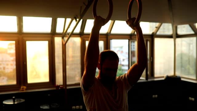 uomo muscoloso che si allena sugli anelli della ginnastica - cura della persona video stock e b–roll