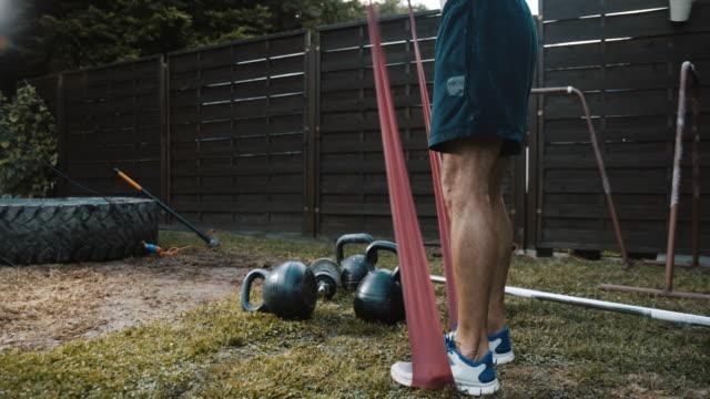 vídeos de stock e filmes b-roll de ds muscular man exercising on the backyard - borracha material de escritório