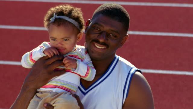 vídeos de stock e filmes b-roll de a muscular man holds a toddler. - desportista