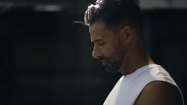 stockvideo's en b-roll-footage met gespierde man maakt zich klaar om oefening in magazijn verlaten - anticipation