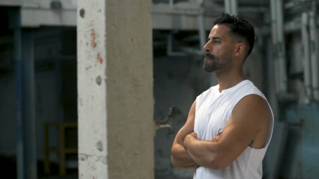 muscular man is getting ready to exercise in abandoned warehouse - anticipation stock videos & royalty-free footage
