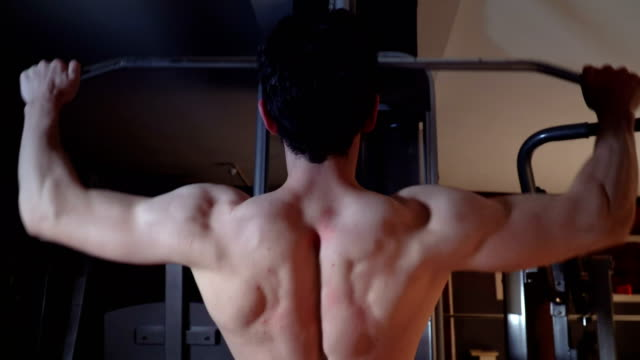 muscular man performing lat pulldown at the gym - lateral pull down weights stock videos & royalty-free footage