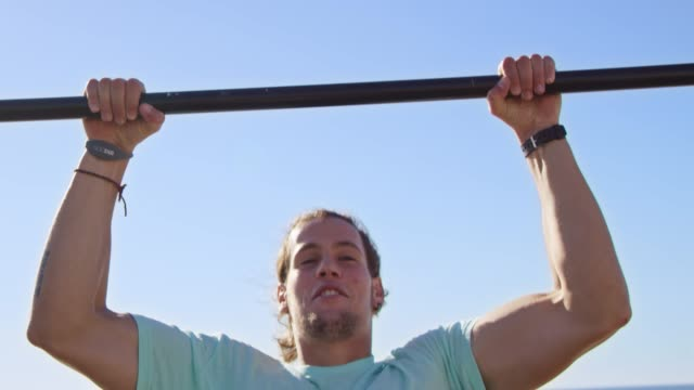 muscular sportsman doing chin-ups at beach - chin ups stock videos and b-roll footage