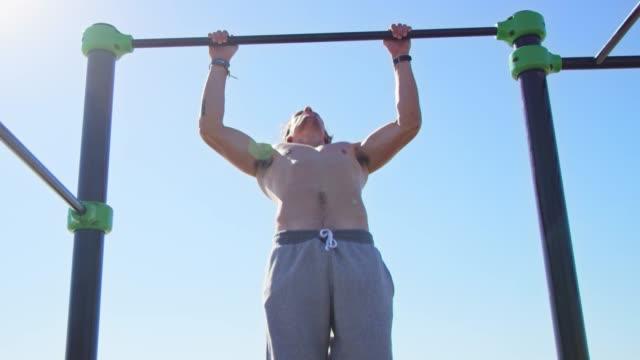 vídeos de stock e filmes b-roll de muscular sportsman exercising on gymnastics bar - treinar
