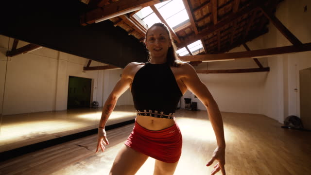 muscular woman posing in a gym dance floor - flexing muscles stock videos and b-roll footage