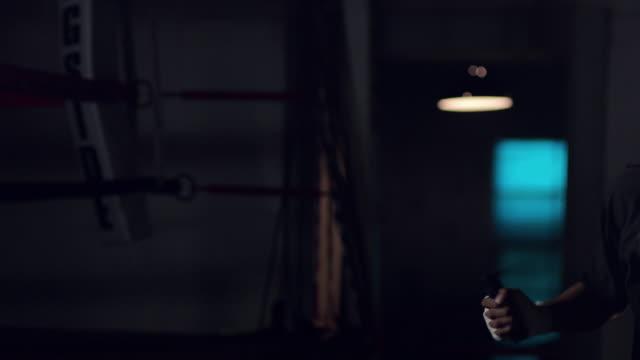 vídeos de stock, filmes e b-roll de slo mo. muscular young boxer jumps rope in a professional boxing gym next to a boxing ring - pouca luz