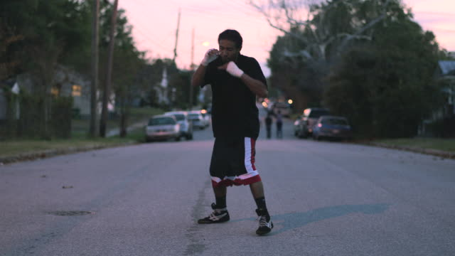 slo mo. muscular young boxer trains by punching the air in the street early in the morning - combat sport stock videos and b-roll footage