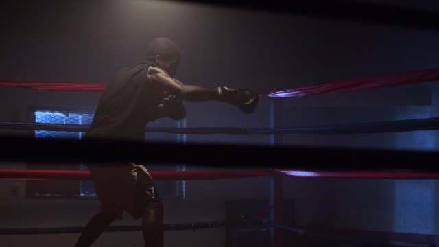 A boxer shadow-boxes in a boxing ring.