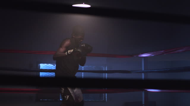 slo mo. muscular young boxer trains by punching the air inside a boxing ring in a professional boxing gym - boxing ring stock videos & royalty-free footage