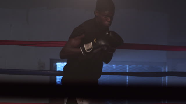 A boxer practices punches and moves in a boxing ring.