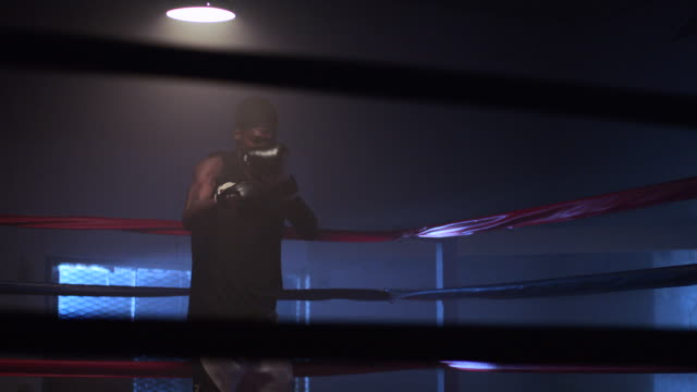 slo mo. muscular young boxer trains by punching the air inside a boxing ring in a professional boxing gym - glove fist stock videos & royalty-free footage