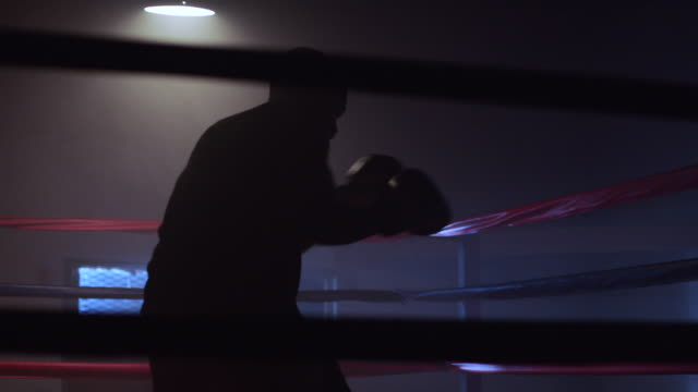 stockvideo's en b-roll-footage met slo mo. muscular young boxer trains by punching the air inside a boxing ring in a professional boxing gym - uithoudingsvermogen