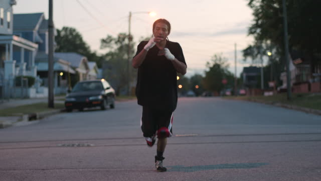 vidéos et rushes de slo mo. muscular young boxer trains by punching the air while running down a street early in the morning - entraînement sportif