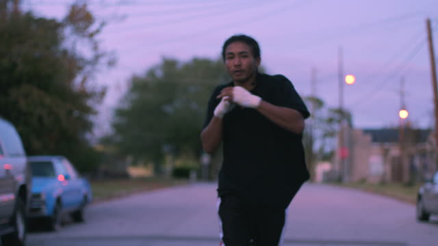 A boxer punches while he runs outdoors.